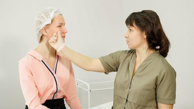 Il terapista professionista in guanti sterili esamina la paziente della clinica di bellezza che tocca le guance e le labbra