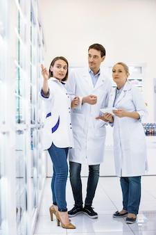 Tre farmacisti professionisti che soggiornano e guardano la vetrina, discutendo di una serie di farmaci