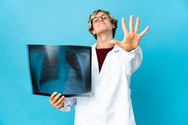 Uomo traumatologo professionista che conta cinque con le dita