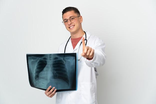 Traumatologo professionista sul muro bianco che mostra e alza un dito