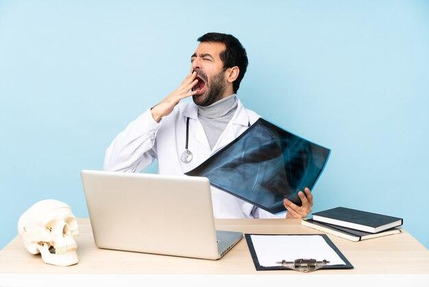 Traumatologo professionista sul posto di lavoro che sbadiglia e copre la bocca spalancata con la mano