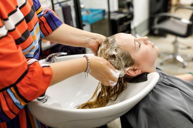 Il parrucchiere professionista irriconoscibile lava i capelli al suo cliente