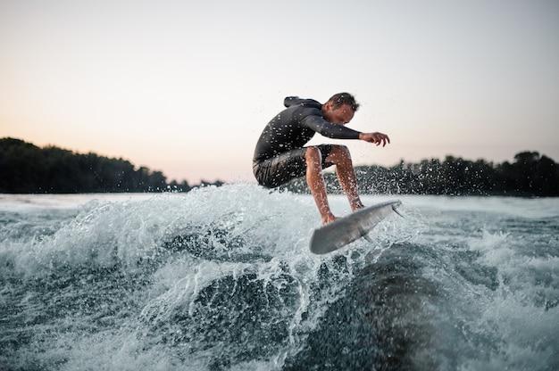 Wakeboarder professionista che salta sull'onda di spruzzi blu sulla priorità alta