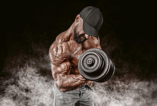 Il sollevatore di pesi professionista si allena in palestra. curl con manubri. concetto di bodybuilding.