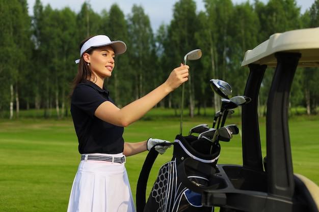 Giocatore di golf professionista della donna che sceglie la mazza da golf dalla sacca.