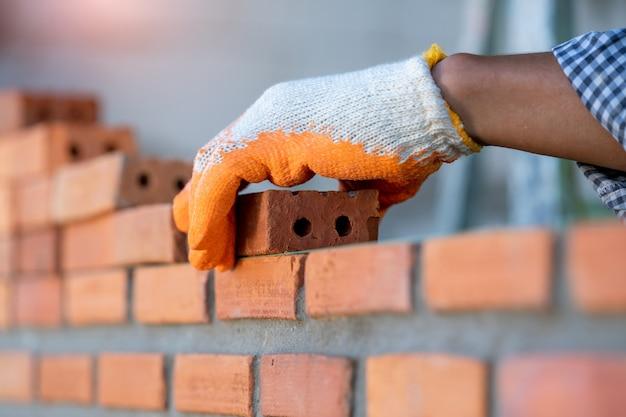 Operaio professionista che costruisce muri di mattoni con cemento