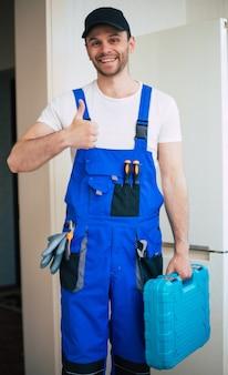 Giovane riparatore professionista in uniforme da lavoratore e cappello con cassetta degli attrezzi moderna con attrezzatura dopo la riparazione del frigorifero in cucina