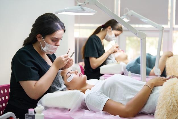Professionisti che lavorano con clienti in un salone di bellezza donna sdraiata su un allenatore cosmetico durante