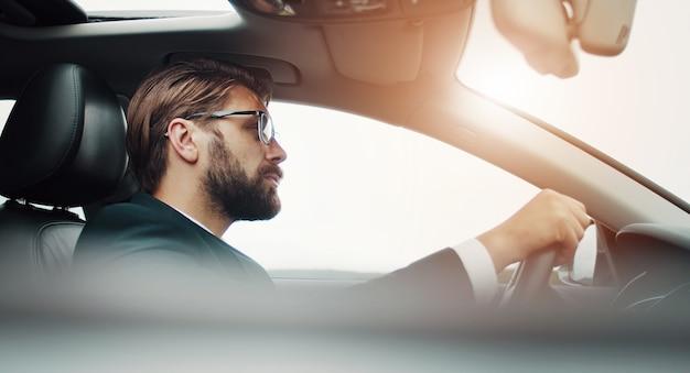 Profilo di uomo d'affari attento seduto dietro la ruota che guida auto