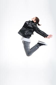 Profilo di un giovane attraente in giacca di pelle nera che salta in alto su sfondo bianco