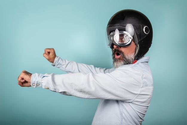 Profilo di hipster barbuto in camicia di jeans con casco e occhiali che finge di guidare una moto, isolato sulla parete blu dello studio.