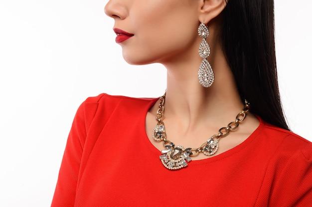 Profilo di una bella donna in abito da sera rosso con collana e orecchini