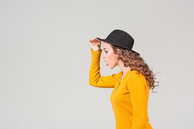 Il profilo della ragazza emotiva con il cappello sul muro grigio