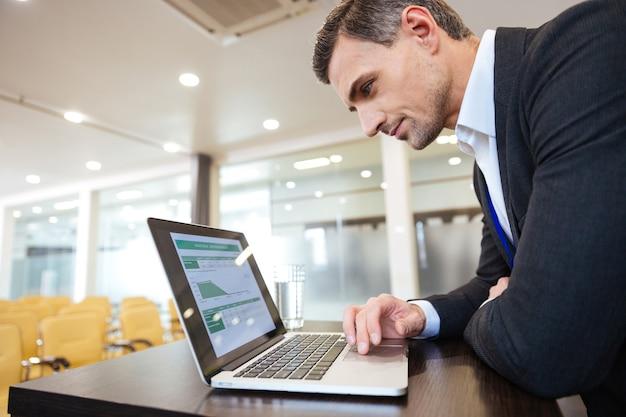 Profilo di un serio uomo d'affari concentrato che lavora con il computer portatile in una sala conferenze vuota empty