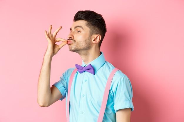 Profilo del ragazzo divertente che tocca i suoi baffi francesi e le labbra arricciate come snob, in piedi compiaciuto su sfondo rosa e guarda a sinistra.