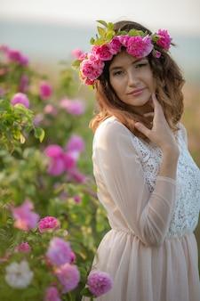 Profilo di una ragazza contro i cespugli di rose selvatiche in fiore con una corona di rose sulla sua testa