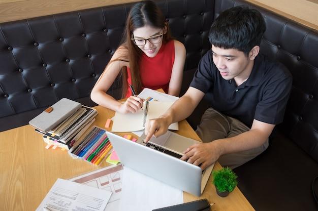 Profilo di una coppia felice che cerca informazioni in linea insieme collegato in un computer portatile all'interno di un caffè con uno sfondo esterno