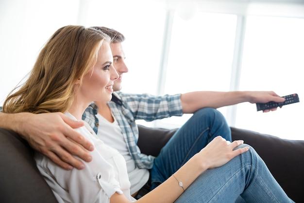 Profilo di coppia felice seduta su ahi e guardando la tv insieme
