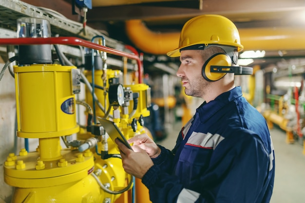Profilo del lavoratore laborioso con casco, antifoni e tuta protettiva che controlla la pressione dell'aria sulle caldaie mentre si trova in un impianto dell'industria pesante