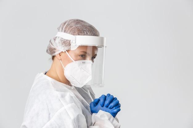 Profilo di promettente dottoressa di mezza età in dispositivi di protezione individuale, visiera, guanti e respiratore, pregando o supplicando.