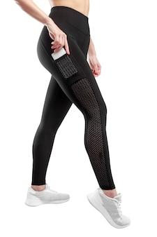 Immagine di profilo di piedi femminili vestiti con leggings neri e scarpe sportive bianche, in posa in studio