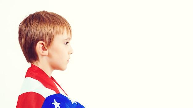 Profilo del piccolo patriota con bandiera americana. il bambino felice tiene una bandiera dell'america.