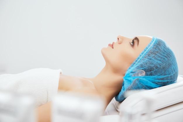 Profilo del modello nel tappo blu sdraiato sul divano in clinica cosmetologica, cosmetologia. modello prima delle procedure cosmetologiche
