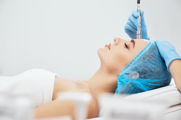Profilo del modello nel tappo blu sdraiato sul divano in clinica cosmetologica con gli occhi chiusi, cosmetologia. mani del medico in guanti blu che fanno procedura di microdermabrasia