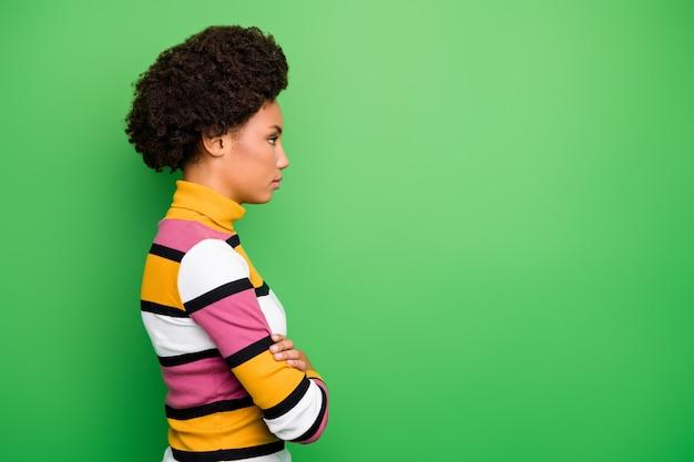 Profilo di bella pelle scura donna d'affari ricci braccia incrociate cercando seriamente spazio vuoto lavoratore responsabile indossare maglione a righe casual