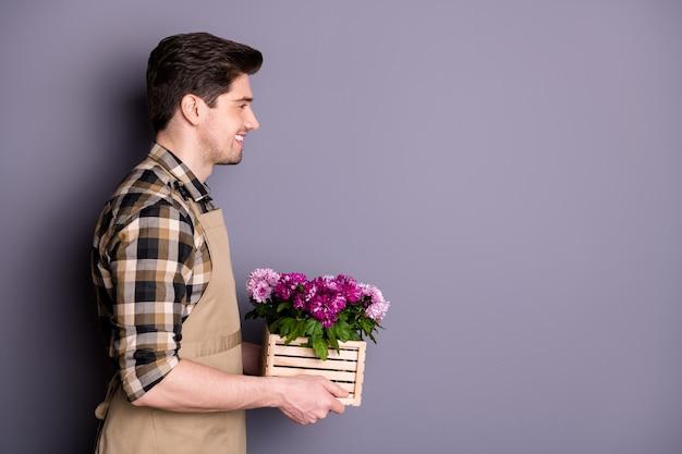 Foto del profilo del ragazzo attraente lavoratore tenere per mano fiori rosa che crescono in vaso consigliando acquistare fiori freschi evitare di tagliare indossare camicia a quadri grembiule isolato muro di colore grigio