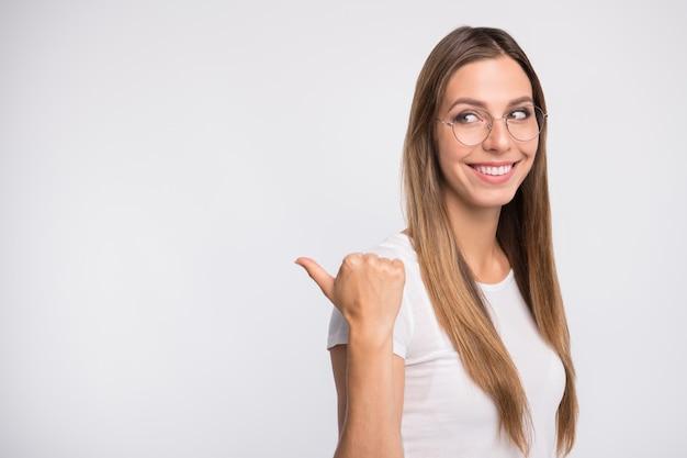 Foto del profilo della signora bruna con gli occhiali in posa contro il muro bianco