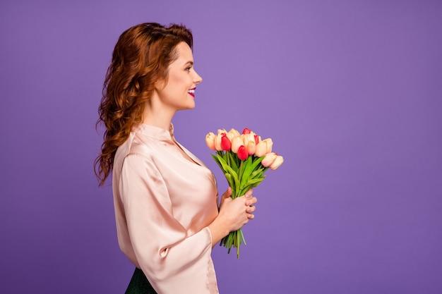 La foto del profilo di una signora affascinante tiene un mazzo di fiori di tulipano che riceve il regalo