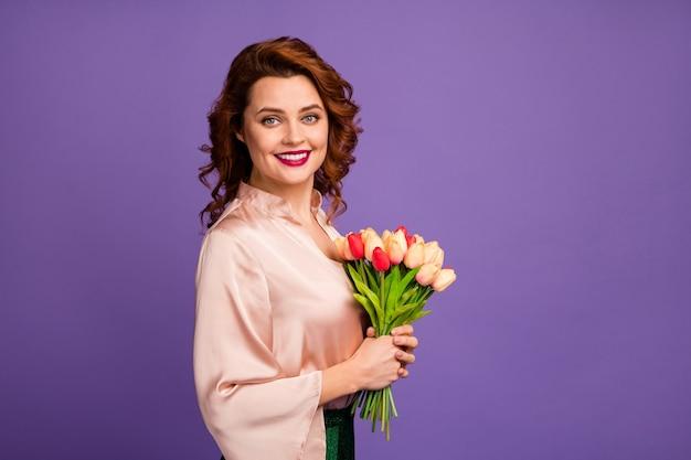 La foto del profilo di un'affascinante signora piuttosto chic tiene un mazzo di fiori di tulipano freschi in regalo