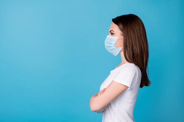 Foto del profilo di donna sicura di sé tenere le braccia incrociate capo lavoratore intelligente carriera guardare lato spazio vuoto indossare maschera medica casual t-shirt bianca isolato colore blu sfondo