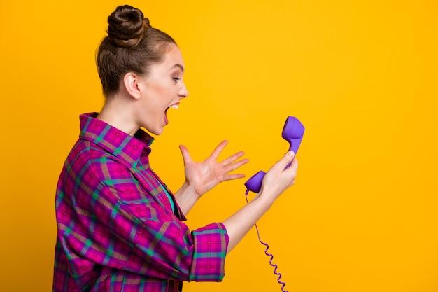 Foto del profilo di una signora furiosa arrabbiata pazza due panini divertenti urlano nel cavo telefonico linea della cornetta cattiva connessione non può parlare il ragazzo indossa una camicia a quadri casual isolato sfondo di colore giallo