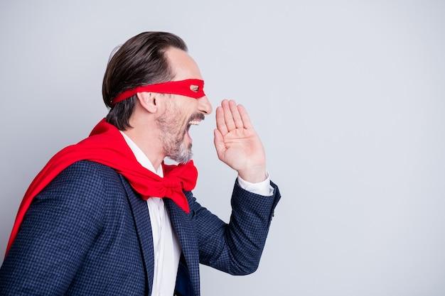 Foto del profilo di pazzo che urla invecchiato maturo uomo d'affari costume da super eroe sguardo urlare novità informazioni spazio vuoto braccio vicino alla bocca indossare tuta maschera viso rosso mantello isolato sfondo grigio