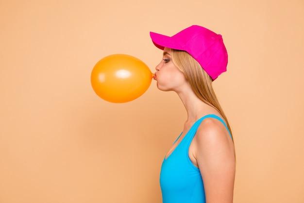 Foto del profilo della ragazza funky che soffia mongolfiera gialla