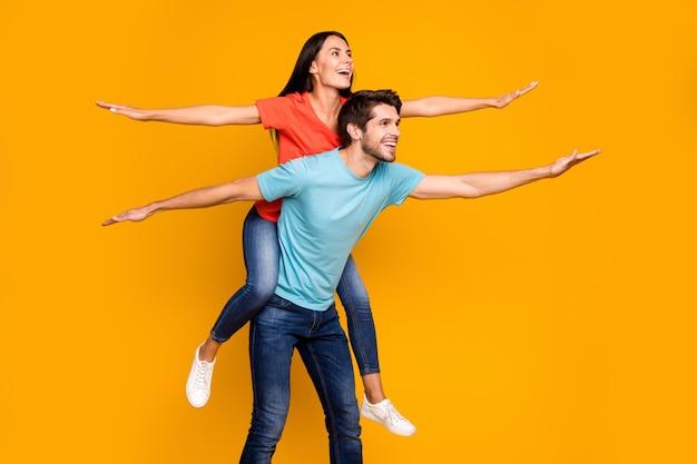 Foto del profilo del ragazzo divertente portare lady piggyback trascorrere l'estate insieme diffondere le mani come ali indossare casual elegante blu arancione t-shirt jeans isolato giallo parete di colore