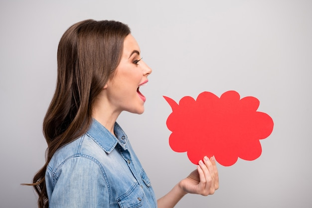 Foto del profilo di una signora abbastanza divertente tenere la mano vuota nuvola di carta vicino a bocca aperta dicendo novità informazioni folla persone indossano jeans casual camicia denim isolato colore grigio