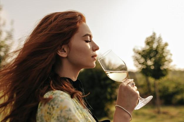 Foto del profilo di una giovane donna dai capelli rossi in eleganti abiti verdi e braccialetto che tiene in mano un bicchiere di champagne e beve all'aperto