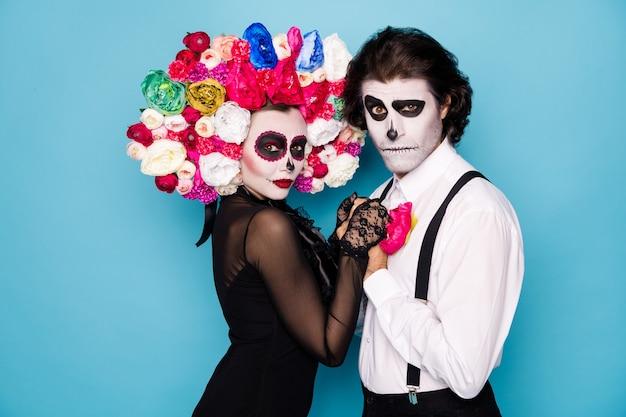 Foto del profilo di coppia spettrale uomo ragazza signora sposata tenersi per mano danza passione tango indossare vestito nero alla moda morte costume decorazioni per il viso rose fascia reggicalze isolato colore blu sfondo