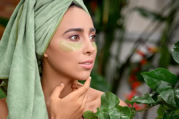 Foto del profilo di una giovane donna bellissima con macchie verdi sotto gli occhi