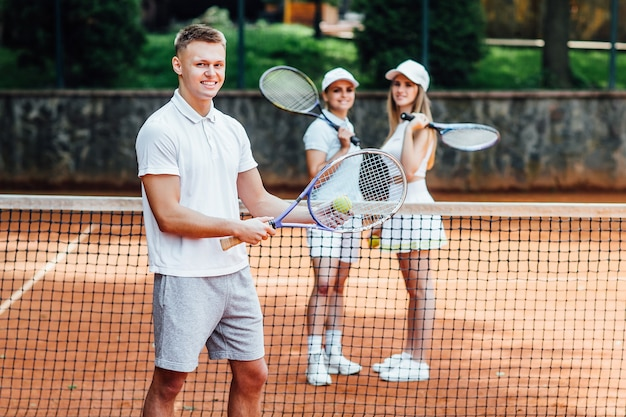 Immagine del profilo di un giovane uomo felice in abiti sportivi, che gioca a tennis, in attesa del servizio, con due ragazze dietro.