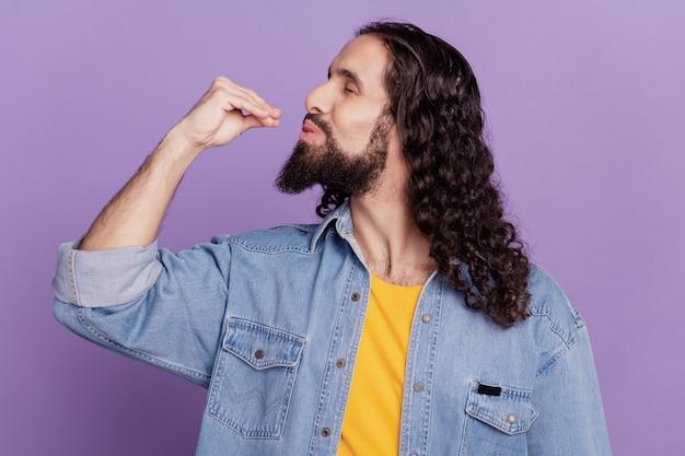 Ritratto di profilo delle labbra delle dita del gesto gourmet dell'uomo barbuto sulla parete viola