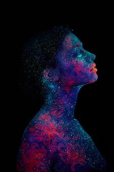 Ritratto di profilo di un alieno bella ragazza. body art ultravioletto blu cielo notturno con stelle e meduse rosa
