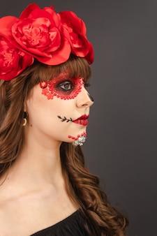 Ritratto di profilo di una bella ragazza con il trucco dia de los muertos con sfondo grigio.