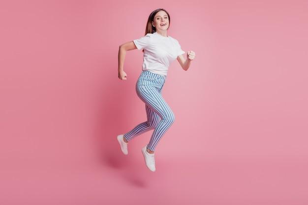 Ritratto di profilo di una ragazza allegra e divertente che salta in aria indossa un abito casual in denim sulla parete rosa