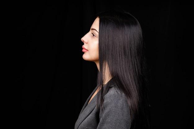 Ritratto di profilo di una ragazza bellissima carina con un sorriso raggiante labbra carnose in abito casual su sfondo nero con spazio vuoto copia spazio.