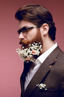 Ritratto di profilo di un uomo barbuto elegante, attraente, alla moda, brutale con fiori in barba, isolato su uno sfondo rosa scuro. vista verticale.