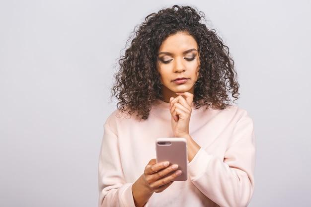 Ritratto di profilo di bella donna di razza mista nera attraente che tiene in mano lo smartphone bianco e lo utilizza con un'espressione seria del viso, alla ricerca di informazioni importanti